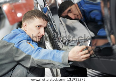 auto repairman worker in automotive industry examining car body painting or repaint at auto repair shop - stock photo