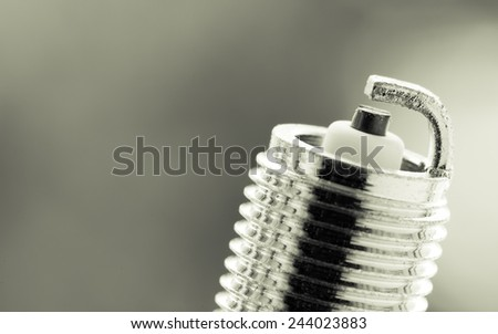 Auto service. New car spark plug as spare part of auto transportation on blurry gray background. - stock photo