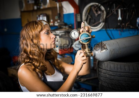 auto service station, working girl. woman in a white headscarf working in the garage - stock photo