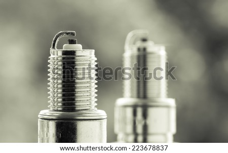 Auto service. Two new car spark plugs as spare part of auto transportation on blurry gray background. - stock photo