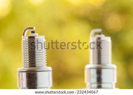 Auto service. Two new car spark plugs as spare part of auto transportation on blurry yellow background. - stock photo