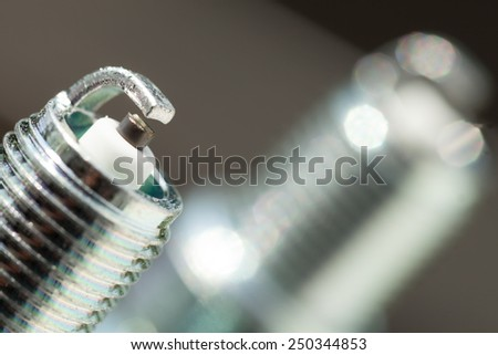 Auto service. Two new car spark plugs as spare part of auto transportation on gray background. - stock photo