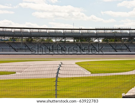 Auto speedway with empty stands and fence - stock photo
