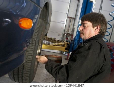 Auto technician works to repair problem with this car's brakes. - stock photo