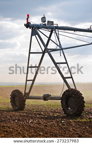 Automated Farming Irrigation Sprinklers System in Operation on Cultivated Agricultural Field - stock photo