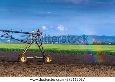 Automated Farming Irrigation Sprinklers System in Operation with Small RAinbow on Cultivated Agricultural Field on a Bright Sunny Summer Day - stock photo