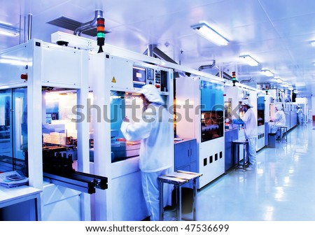 Automated production line in modern Solar silicon factory. Slow shutter speed with figures in motion. - stock photo