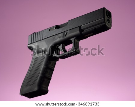 automatic hand gun on pink background, loaded position - stock photo