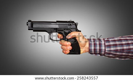 Automatic pistol handled with one hand - grey gradient background - stock photo