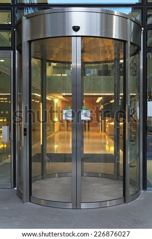 Automatic revolving door at office building - stock photo