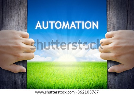Automation. Hand opening an old wooden door and found Automation word floating over green field and bright blue Sky Sunrise. - stock photo