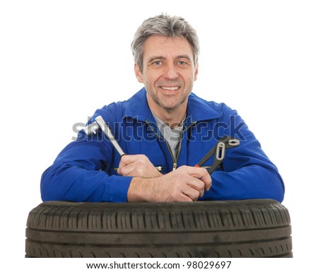 Automechanic leaning on car tires. Isolated on white - stock photo