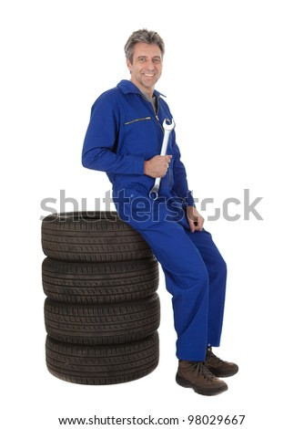 Automechanic sitting on car tires. Isolated on white - stock photo