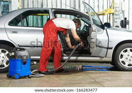 Automobile cleaning theme. Mechanic hoovering the car cabin with vacuum cleaner at auto repair shop garage - stock photo
