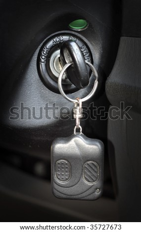 Automobile key with a charm inserted into the lock of ignition of the car - stock photo
