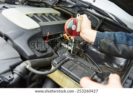 automobile mechanic tests car antifreeze liquid for winter and summer - stock photo