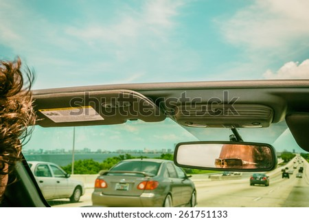 Automobiles on highway young man wearing sunglasses vintage filter image  Male car driver in open retro cabriolet reflected shades in rearview mirror concentrated on rush hour traffic - stock photo