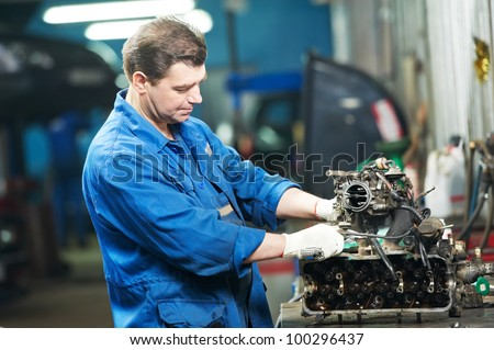 automotive mechanic disassembling car engine with spanner during automobile maintenance at repair service station - stock photo