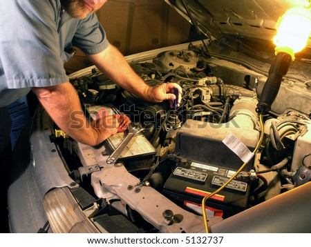 Automotive technician doing repair job. - stock photo