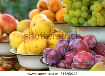Autumn abundance in the village. Fruit and vegetables like apples, pears, plums, peaches, grapes, tomatoes, cucumbers and homemade preservation. - stock photo