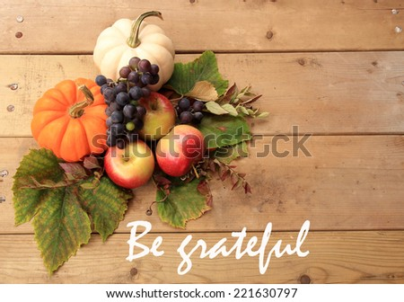 "Autumn and Thanksgiving concept. Seasonal fruit and pumpkins on wood background with the phrase ""Be grateful"" in the center.  - stock photo"
