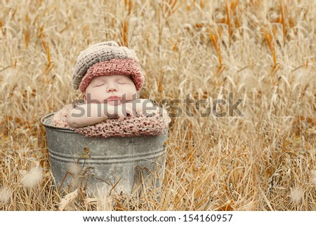 Autumn baby sleeping in a bucket for a portrait. - stock photo