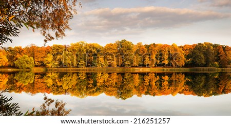 Autumn background, panoramic view of calm lake and trees in the park at the sunset  - stock photo