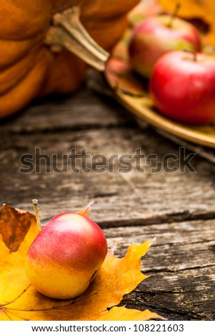 Autumn background with apples, pumpkin and maple leaf on old wooden table. Thanksgiving day concept. Shallow depth of fields - stock photo