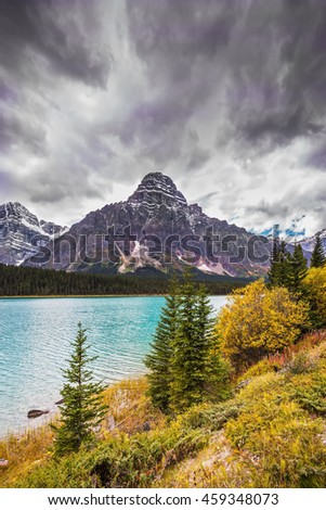 Autumn Bow River in Banff National Park, Canada. Azure waters of the river are surrounded with Rocky Mountains and magnificent autumn yellow and orange vegetation - stock photo