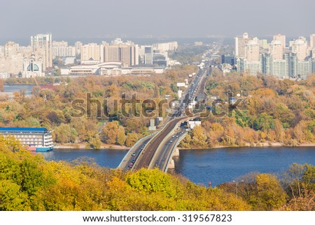 Autumn cityscape with yellowed leaves on the trees, the river and the bridge across it in the foreground, urban buildings and sky in the background. Kiev, Ukraine.  - stock photo