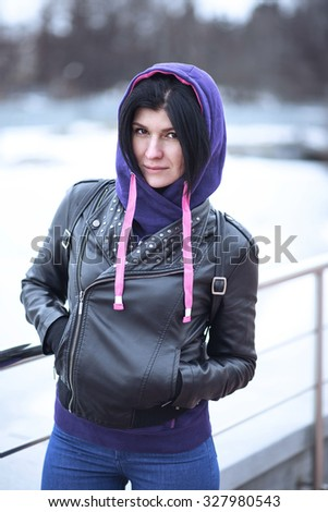 Autumn cloudy lifestyle. Portrait of a stylish young hipster woman on a street in the city, posing in a black leather jacket with leather. Close-up. Resting in the fresh air. The girl brunette. - stock photo