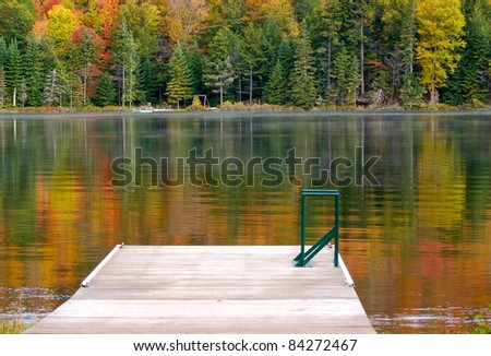 Autumn colors are reflected in the  calm lake waters - stock photo