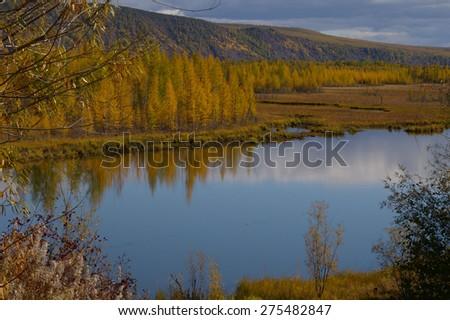 Autumn colors surround a lake - stock photo