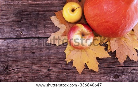 Autumn composition with pumpkin, yellow maple leaves and apple on rustic wooden table. Thanksgiving holiday and harvest concept. Top view. Toned image - stock photo