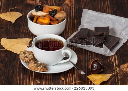 Autumn Concept. Cup Of Tea Or Coffee. Dried Fruits. Dark Chocolate. Wooden Background. - stock photo