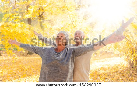 autumn couple  with outstreched arms - stock photo