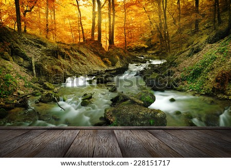 Autumn creek woods with yellow trees foliage and rocks in forest mountain and wood pier - stock photo