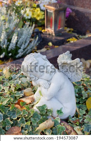 Autumn decoration on the tomb with white angel. - stock photo