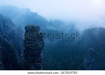 Autumn early morning view over sandstone rocks to fall valley of Saxony Switzerland. Sandstone peaks and hills increased from heavy mist.  - stock photo