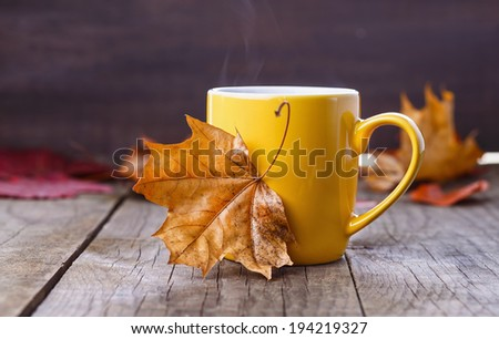 Autumn (fall) cup of tea and colorful leaves over rustic wooden background. Selective focus, shallow dof - stock photo