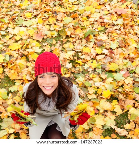 Autumn / Fall leaves background with woman happy looking up sitting on autumn leaves in colorful fall forest foliage. Beautiful girl with copy space. Mixed race Asian Chinese / Caucasian female model. - stock photo