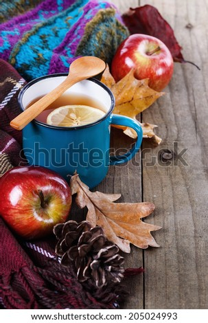 Autumn (fall) still life: lemon tea, apples and colorful leaves over rustic wooden background - stock photo
