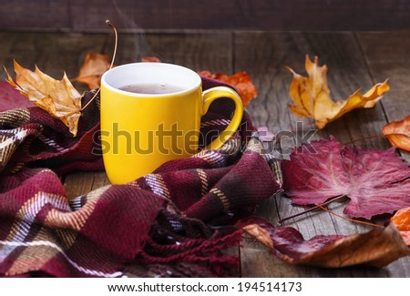 Autumn (fall) still life with cup of tea, warming scarf and colorful leaves over rustic wooden background. Selective focus, shallow dof - stock photo