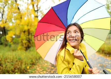 Autumn / fall - woman happy with umbrella in rain walking in forest. Girl enjoying rainy fall day looking away smiling. Mixed race Caucasian / Asian chinese girl. - stock photo