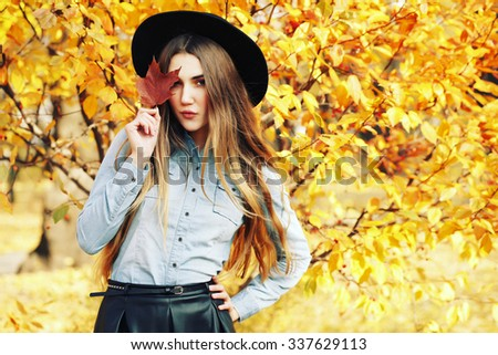 Autumn fashion portrait of glamour sensual young stylish lady wearing trendy fall outfit, black hat, denim shirt and leather skirt. Beautifull model with long healthy ?olorful ombre hair outdoors. - stock photo