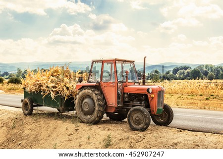 Autumn field works -Tractor laden with dry stalks of corn - stock photo
