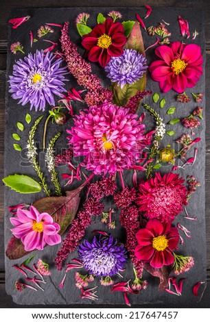autumn flowers composition with asters, dahlias, herbs and leafs on  dark table , floral background - stock photo
