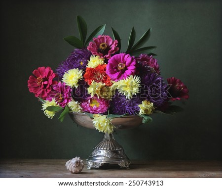 autumn flowers in an iron vase and a cockleshell - stock photo