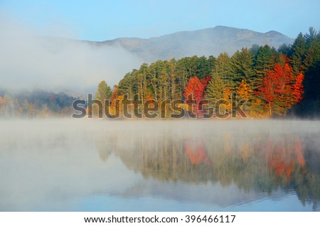 Autumn foliage and fog lake in morning - stock photo