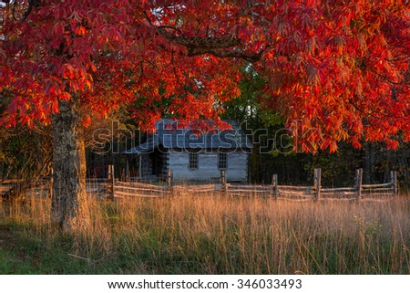 Autumn foliage frames this old one room schoolhouse in the Cumberland Gap National Park. - stock photo